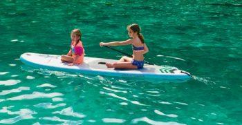 2 young girls paddle boarding in clear blue water.